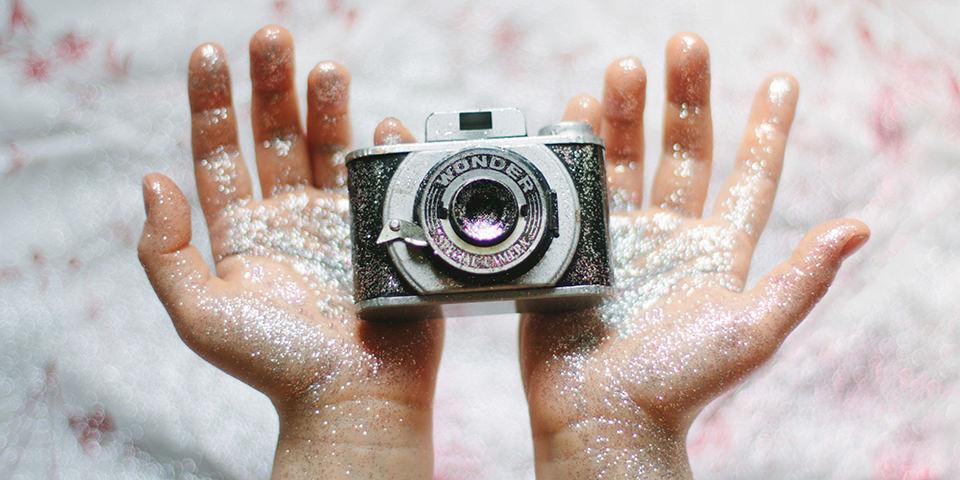 Eine Kamera in verglitzerten Händen.