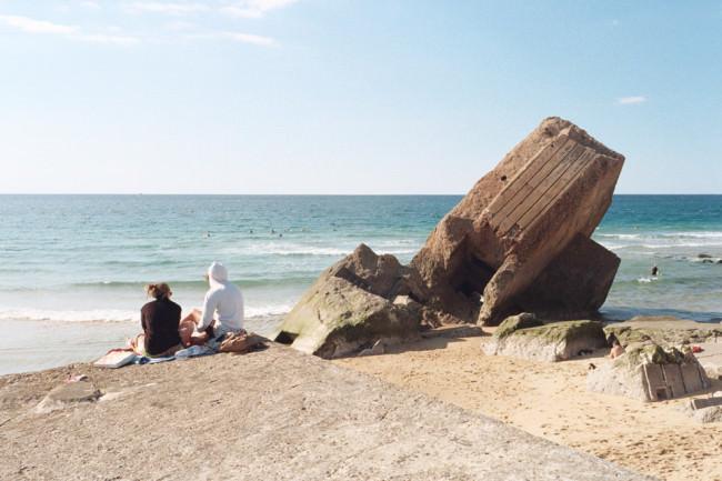 Strandbesucher neben einem Bunker mit Blick aufs Meer.