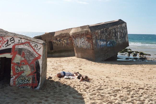 Strandbesucher liegen vor einem Bunker.