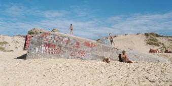 Kinder spielen auf einem Bunker am Strand.