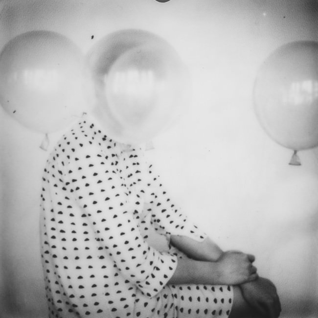 Eine Frau in Seitenansicht und Luftballons.