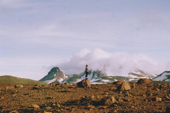 Eine Frau steht auf einem großen Stein.