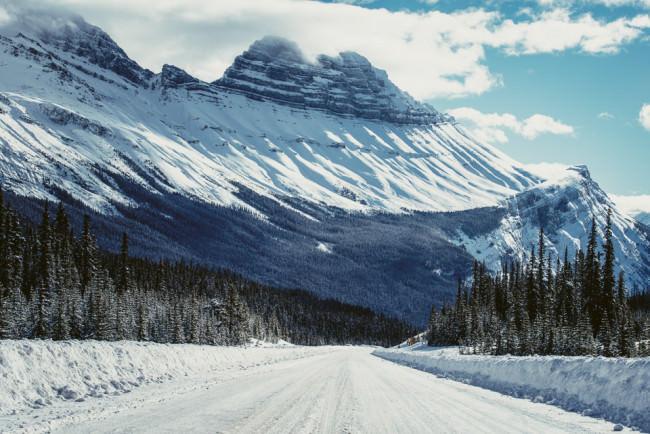 Schneebedecktes Gebirge vor Nadelwald und einer darauf zuführenden Straße.