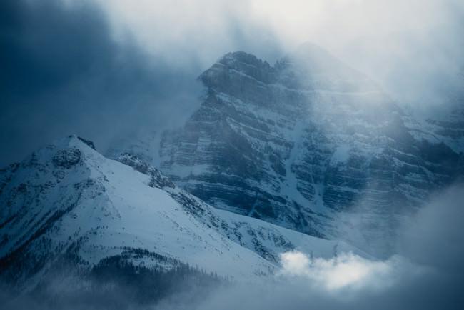 Schneebedecktes Gebirge in Dunst und Wolken.