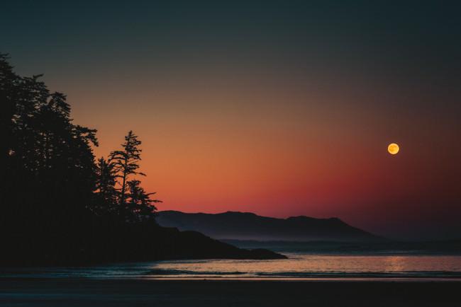 Goldener Mond über einer Strandlandschaft bei Sonnenuntergang.