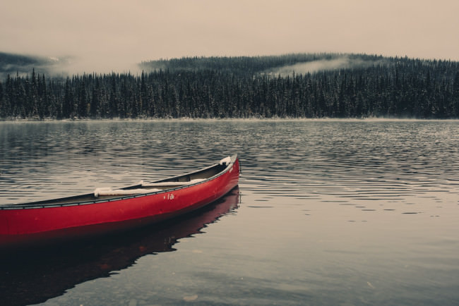 Schneebedecktes Boot auf einem See, im Hintergrund ein Nadelwald.