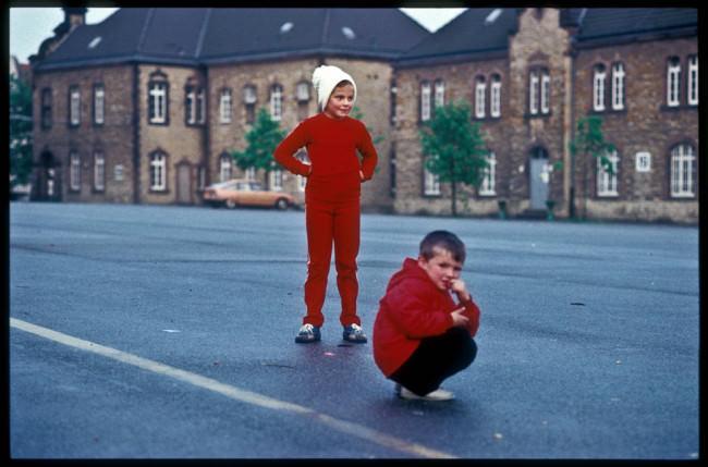 Kinder in roten Sachen stehen auf der Straße.