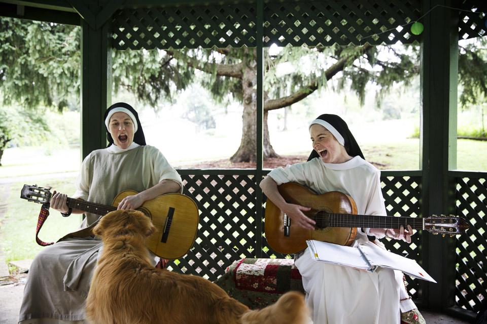 Zwei Nonnen spielen Gitarre, ein Hund ist auch dabei.