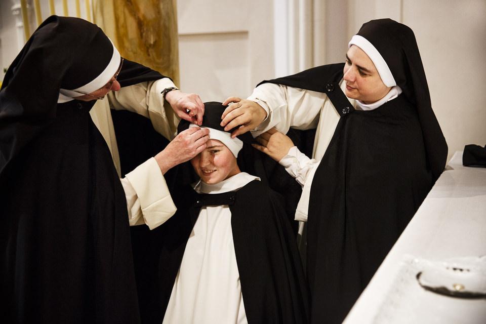 Eine Nonne bekommt von zwei weiteren Nonnen eine neue Haube.