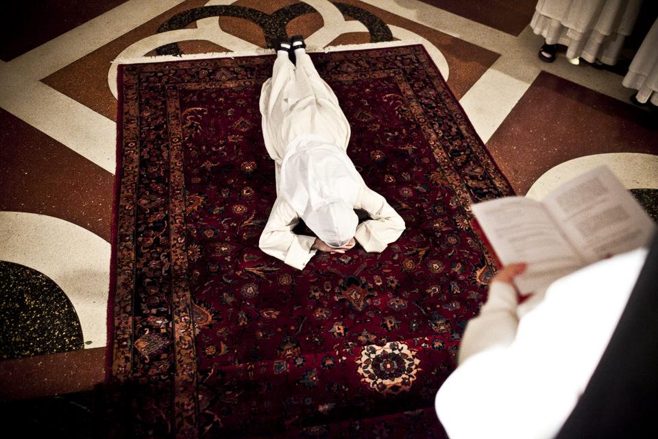 Einne Nonne liegt bauchwärts auf dem Boden, eine andere schaut in ein Buch.