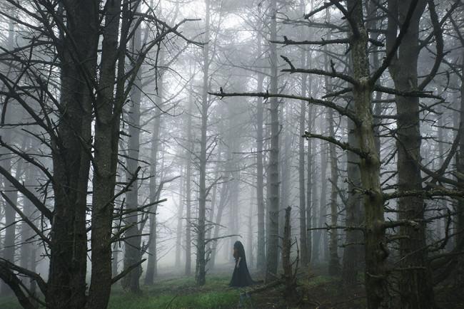 Eine Frau mit Kutte im Wald