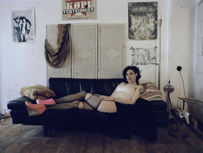 Frau liegt auf dem Sofa.