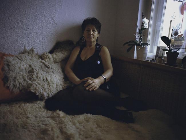 Frau sitzt auf dem Bett.