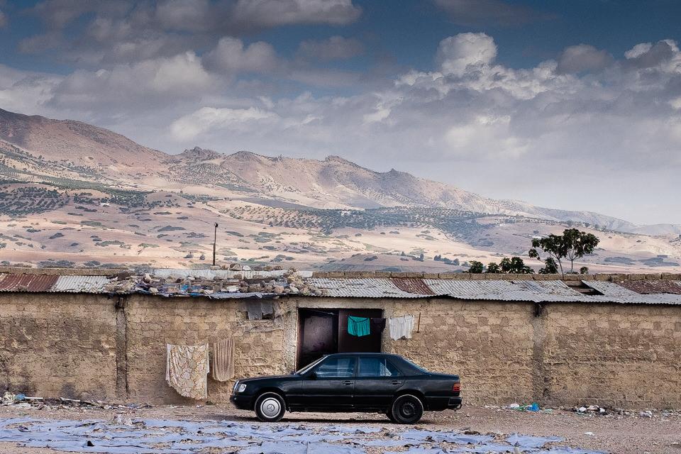 Ein alter Benz steht vor alten Häusermauern.