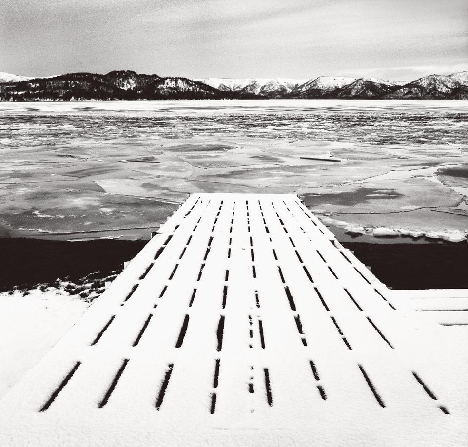 Ein Steg führt auf einen vereisten See.