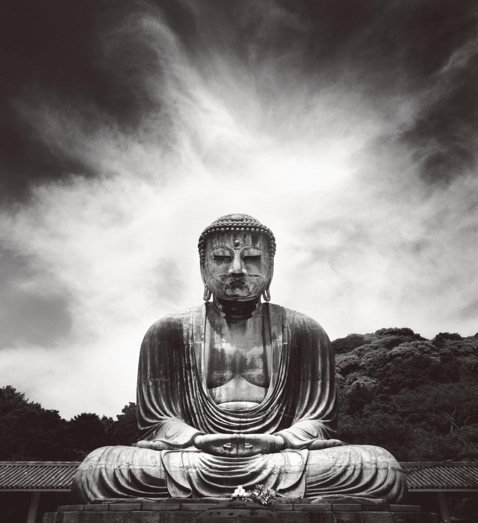 Eine Buddha-Statue vor dramatischen Wolken.