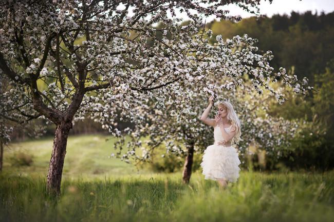 Eine Braut vor blühenden Bäumen.