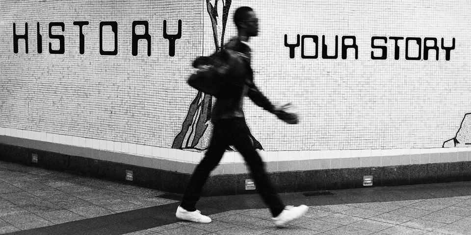 Eine Person läuft vor einem Schriftzug vorbei