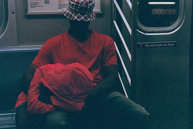 Ein Kind schläft in der Bahn auf dem Schoß eines Erwachsenen