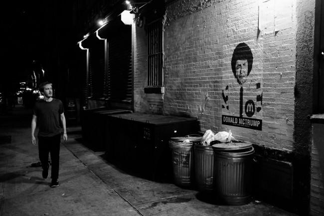 Eine Person betrachtet im vorbei Gehen ein Graffiti