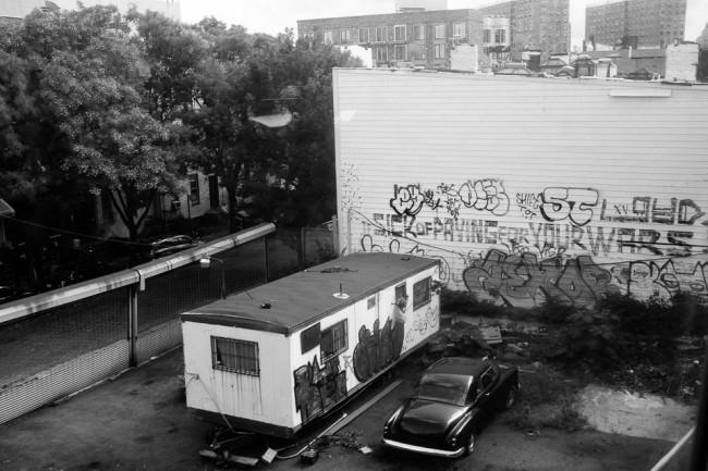 Ein Wohnwagen und ein Auto stehen vor einer bemalten Wand