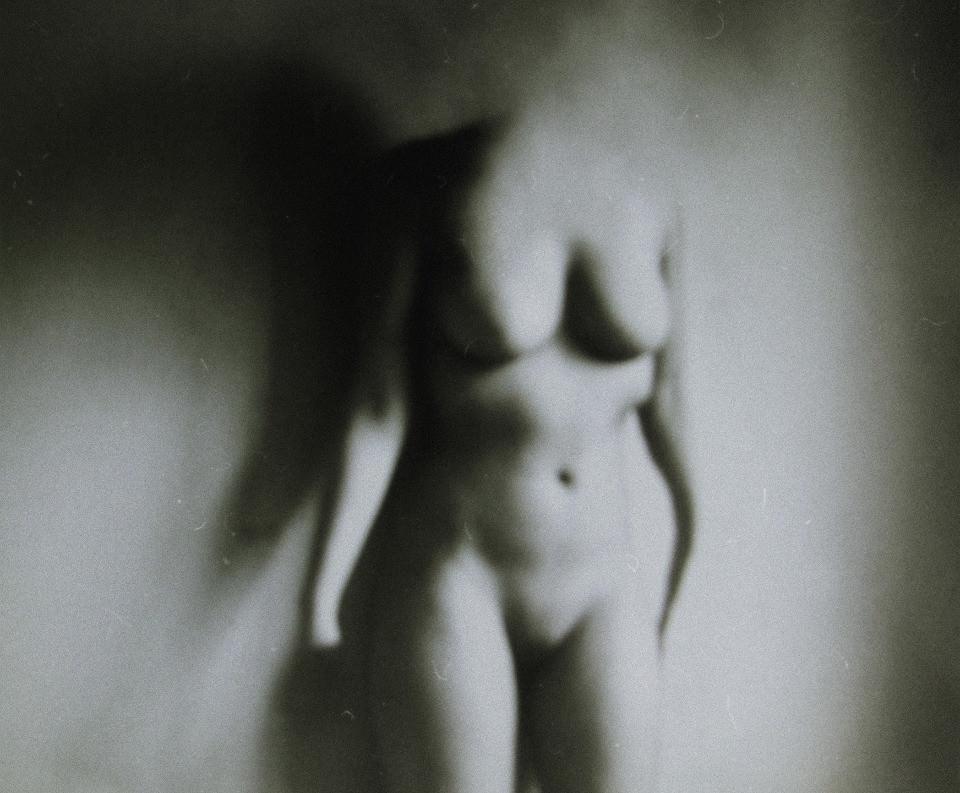 Eine nackte Frau verschwimmt an der Wand hinter ihr.