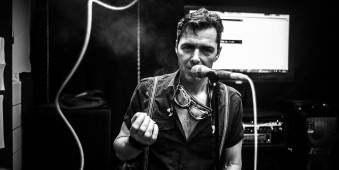 Ein Mann raucht und steht an einem Mikrofon