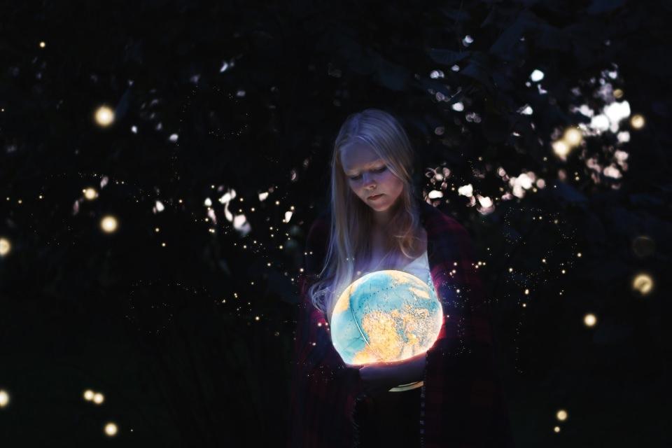Ein Mädchen hält im Dunkeln einen beleuchteten Globus im Arm, der ihr Gesicht erhellt.