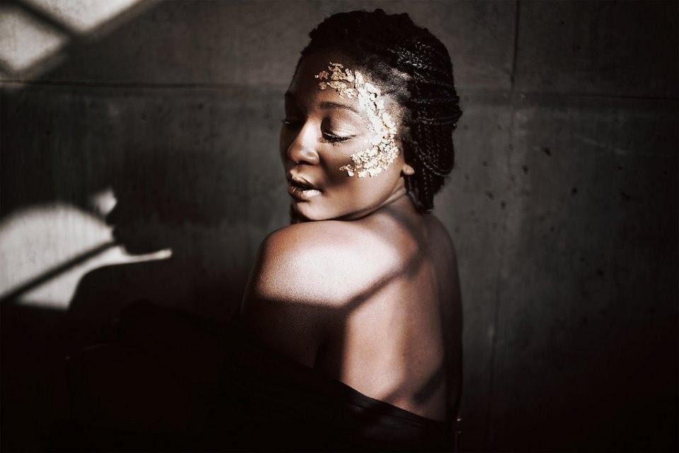 Portrait einer Frau mit Blattgold im Gesicht, Schattenspiel auf ihrer Haut.