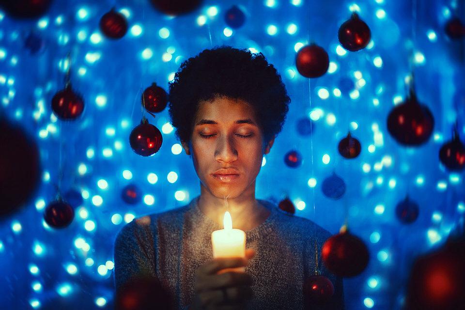 Ein Junge mit einer Kerze, umringt von Weihnachtskugeln.