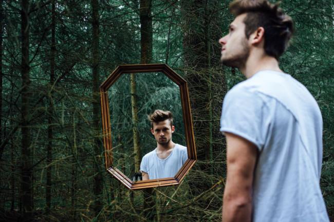 Ein Mann in einem Spiegel macht ein anderes Gesicht.