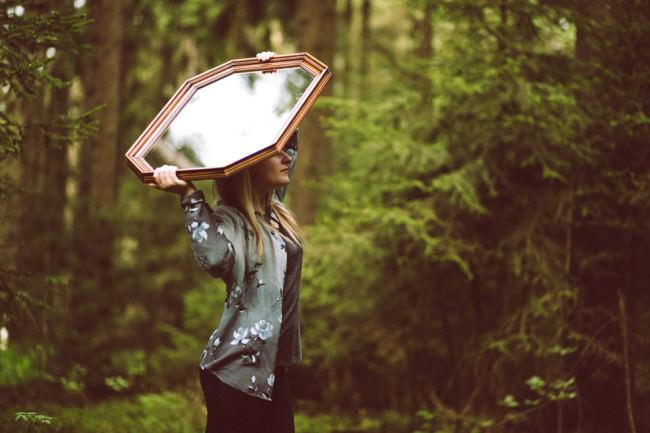 Eine Frau hält einen Spiegel hoch.