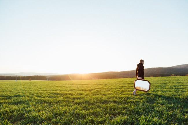Ein Feld, Sonnenuntergang, eine Person trägt einen Spiegel.