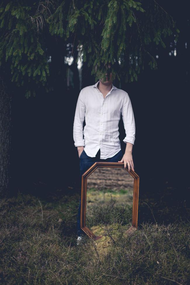 Ein Mann, versteckt, hält einen Spiegel vor sich.