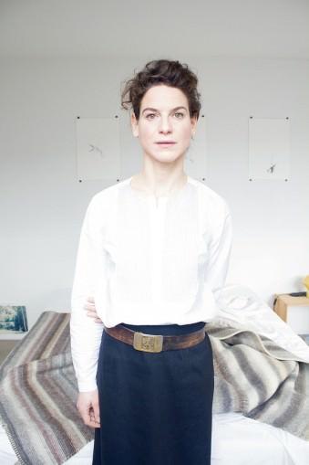 Portrait einer Frau in weißer Bluse vor einem hellen Zimmer.