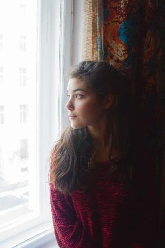 Portrait einer Frau, an einem Fenster sitzend.