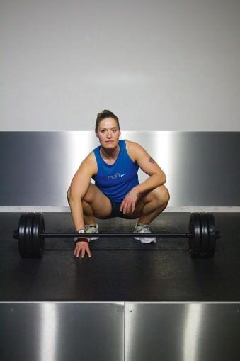 Portrait einer Frau in Sportkleidung, hinter einer großen Hantel hockend.