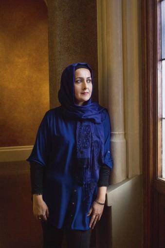 Portrait einer in dunkelblau gekleideten Frau, an einer Säule lehnend.