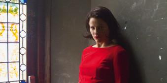 Portrait einer Frau mit rotem Oberteil vor dunkler Wand, links ein Fenster.