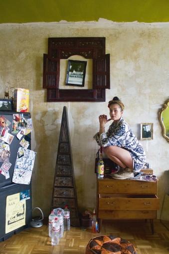 Portrait einer Frau, die auf einem Schubladenschrank sitzt, ringsherum ein Zimmer mit unterschiedlichen Einrichtungsgegenständen.