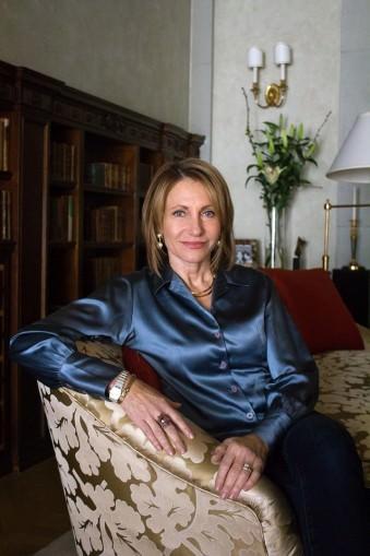 Portrait einer Frau in einem Sessel sitzend in einem gehoben eingerichteten Zimmer.