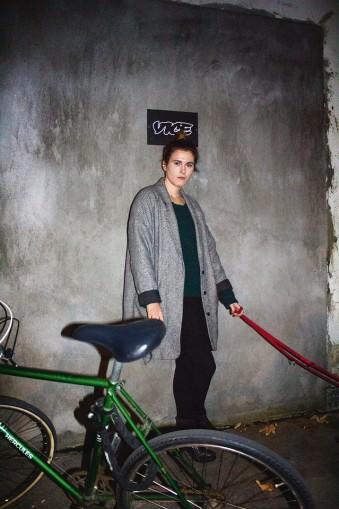 Portrait einer Frau mit Hundeleine vor Betonwand, im Vordergrund ein grünes Fahrrad.