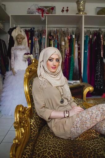 Portrait einer Frau mit Kopftuch, in einem Geschäft für Damenkleider sitzend.