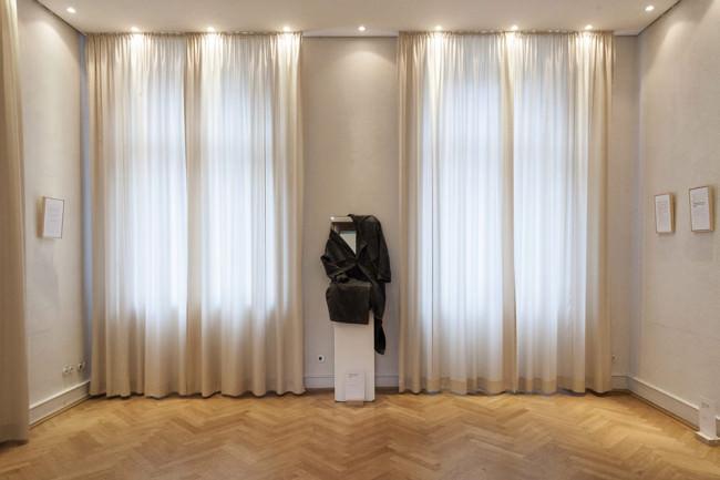 Eine Ausstellung, Fenster, Gardinen und ein Objekt.