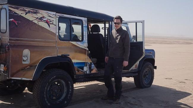 Ein Mann steht vor einem Geländefahrzeug in der Wüste.