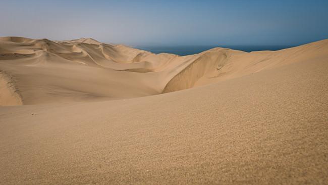Wüstenkämme, dahinter blauer Dunst am Horizont.