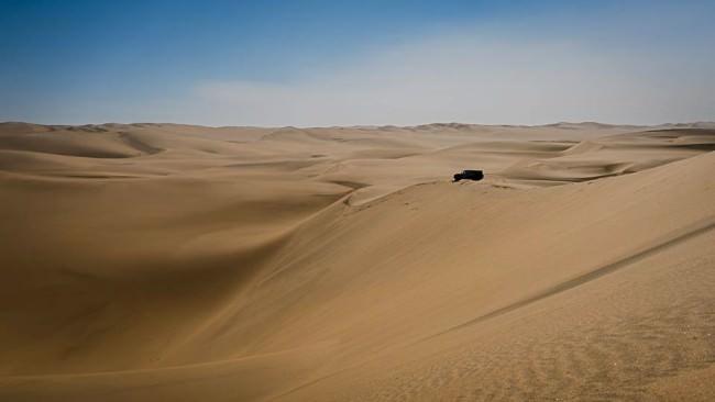 Ein Geländefahrzeug steht auf einer Düne in der Wüste.
