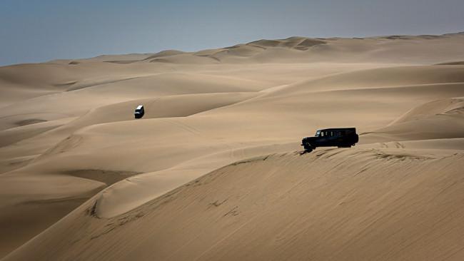 Zwei Geländefahrzeuge stehen auf Dünen in der Wüste.