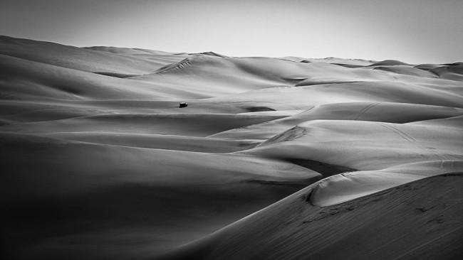 Ein Geländefahrzeug fährt durch eine Wüste.