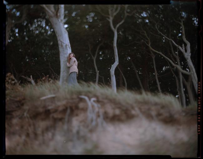Eine Frau lehnt an einem Baum.